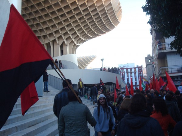 Protesters in Seville carry the anarchist red and black flag past Las Setas, 'The Mushrooms', January 2012