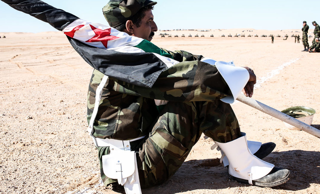 A soldier is resting with Western Sahara's flag
