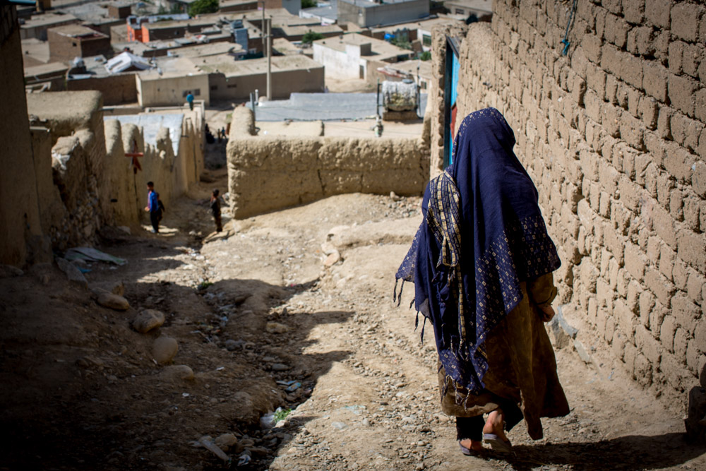 A widow walks downhill to her home in a poor suburb of Kabul