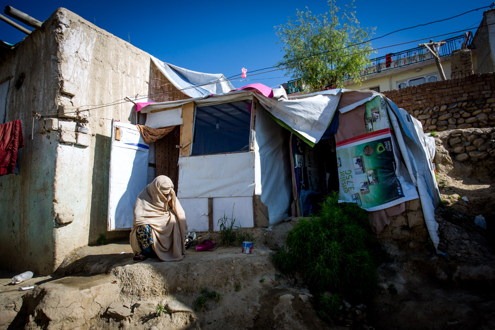 A widow crouches outside of her tiny, makeshift home