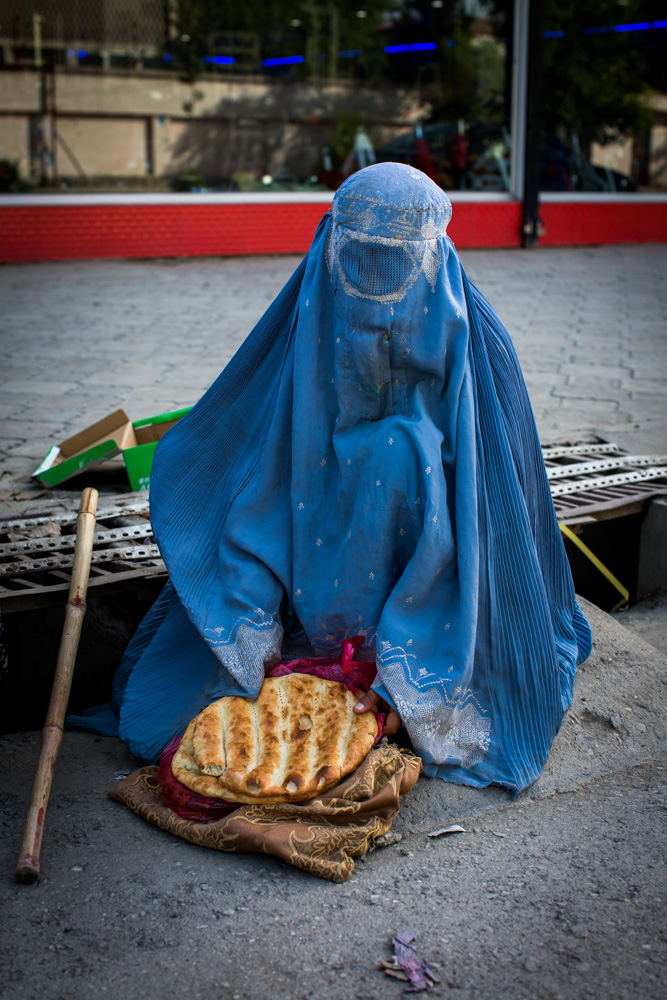 A widow begs on a busy road in Kabul; the two loaves of bread she now has are the dinner for her family of eight.