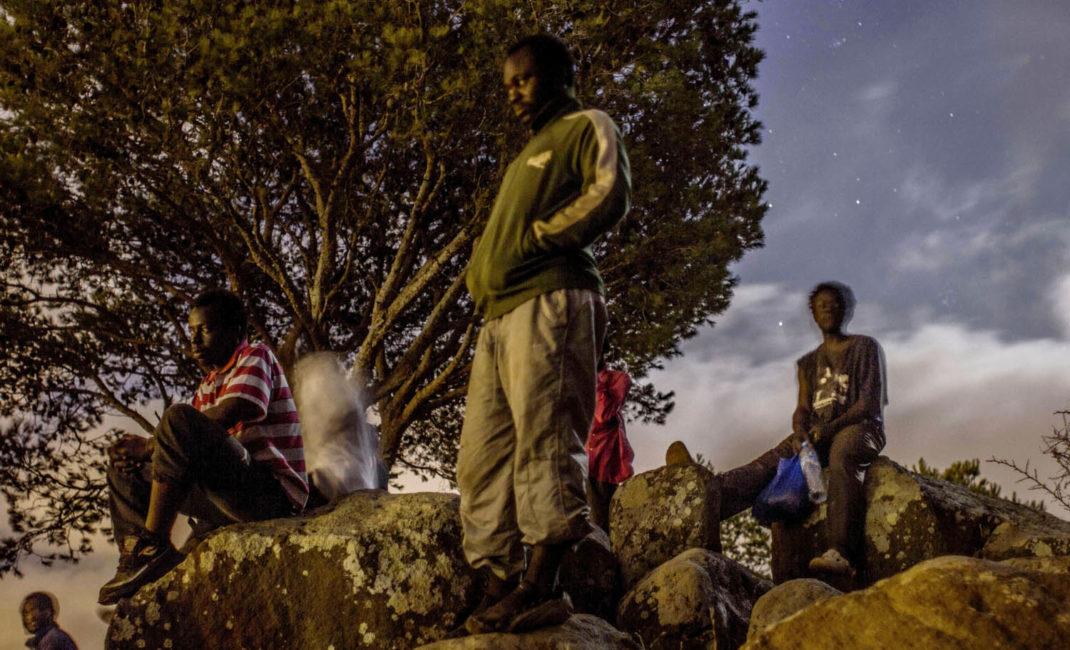 0001unos cameruneses miran las luces que desprende Melilla, des de lo alto del monte gurugu