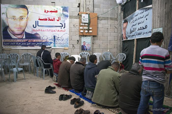 Friends and relatives praying for al-Qiq's release - Photo by Jordan Siegel