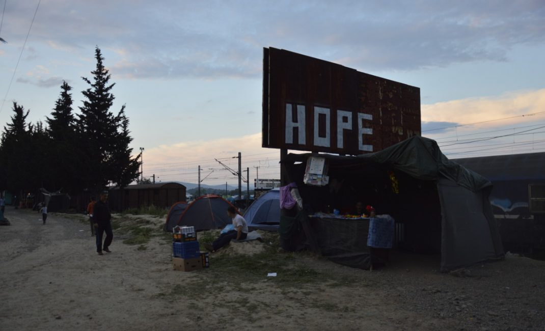"A rusty billboard with ""Hope"" written on it. Underneath, a small shop ran by a refugee"