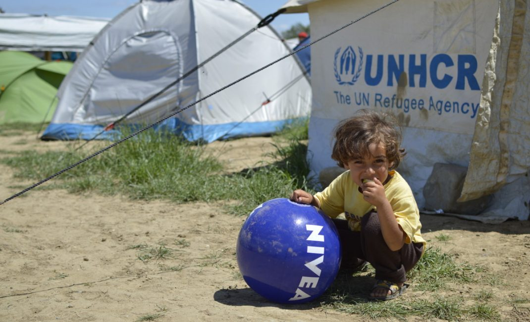 A child eats an apple leaning on a ball near a tent donated by UNHCR