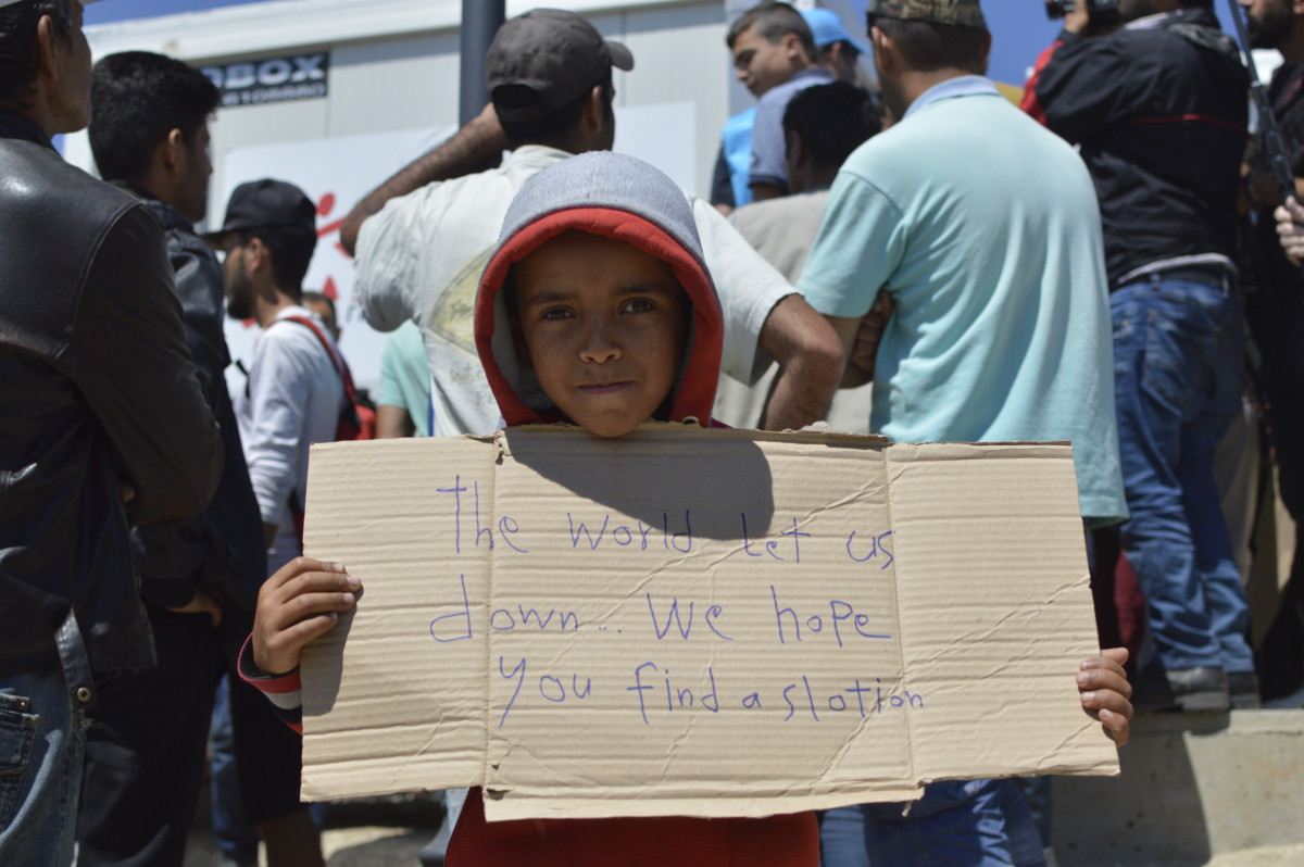 "A kid shows a cardboard with ""The world let us down...we hope you find a s[o]lution"" written on it, during a peaceful manifestation at Idomeni, when a Europe Union delegation visited the makeshift camp"