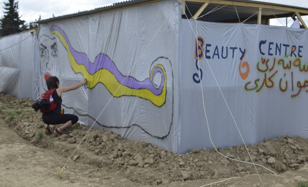 A volunteer draws a graffiti on a tent that will be used as a beauty centre by the women of the camp