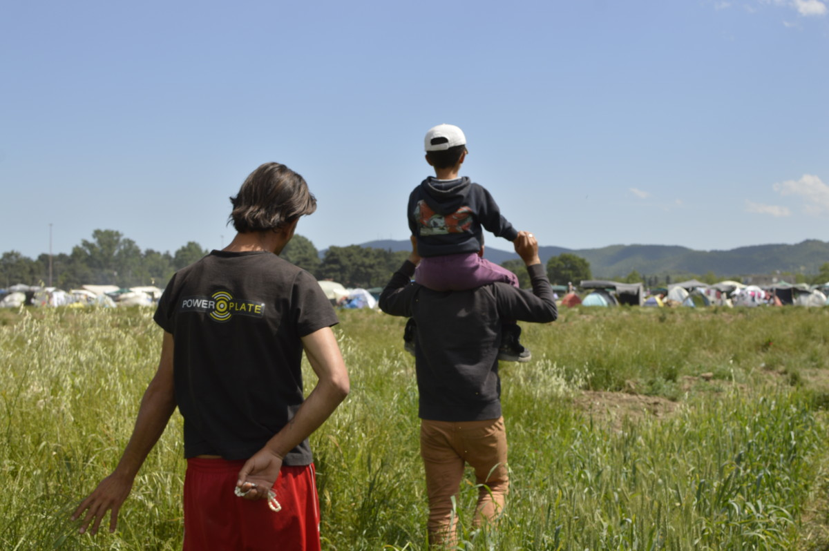 Two men, one of them with his kid on the shoulders, get back to their tent after they went for a stroll near the barbed wire of the Macedonia-Greece border