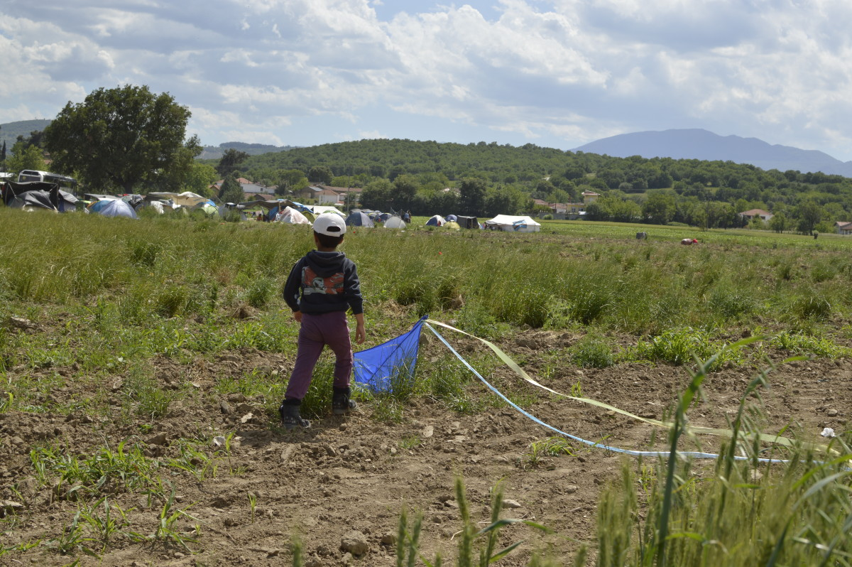 A kid plays with his kite away from the settlement of Idomeni