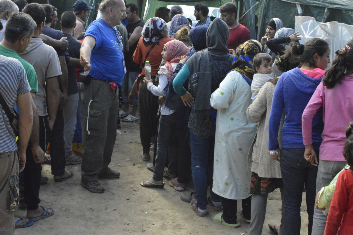 A volunteer divide men's queue from the women and children's one during a clothes distribution
