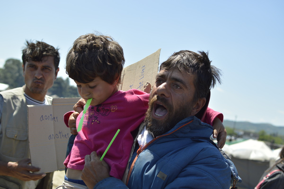 A refugee address other Idomeni refugees during a manifestation holding his child