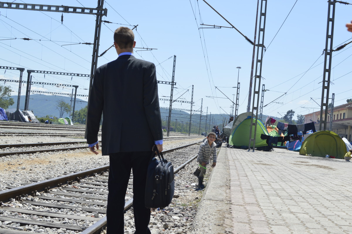 A kid looks curiously at a dressed-up man with an overnight bag on the rail of the Idomeni station