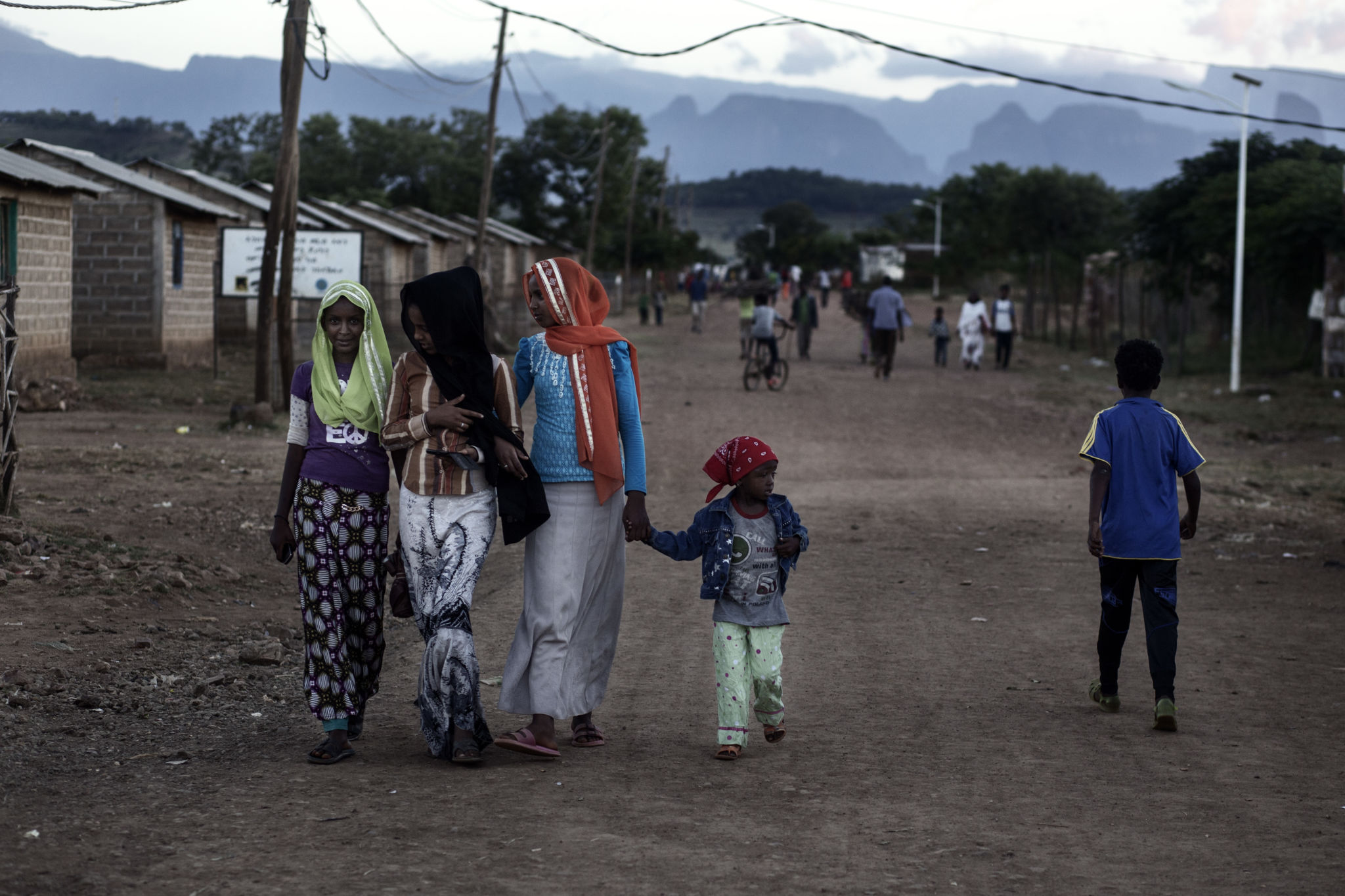 Three young women walking along a dirt road with a toddler.