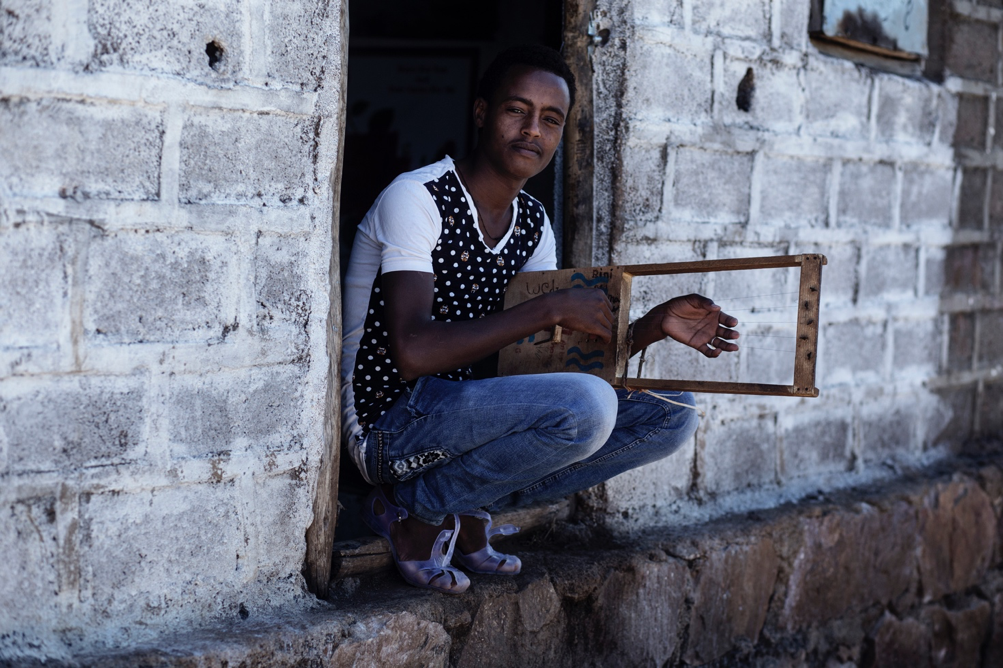 Teenage boy crouching in a doorway and playing Eritrean guitar