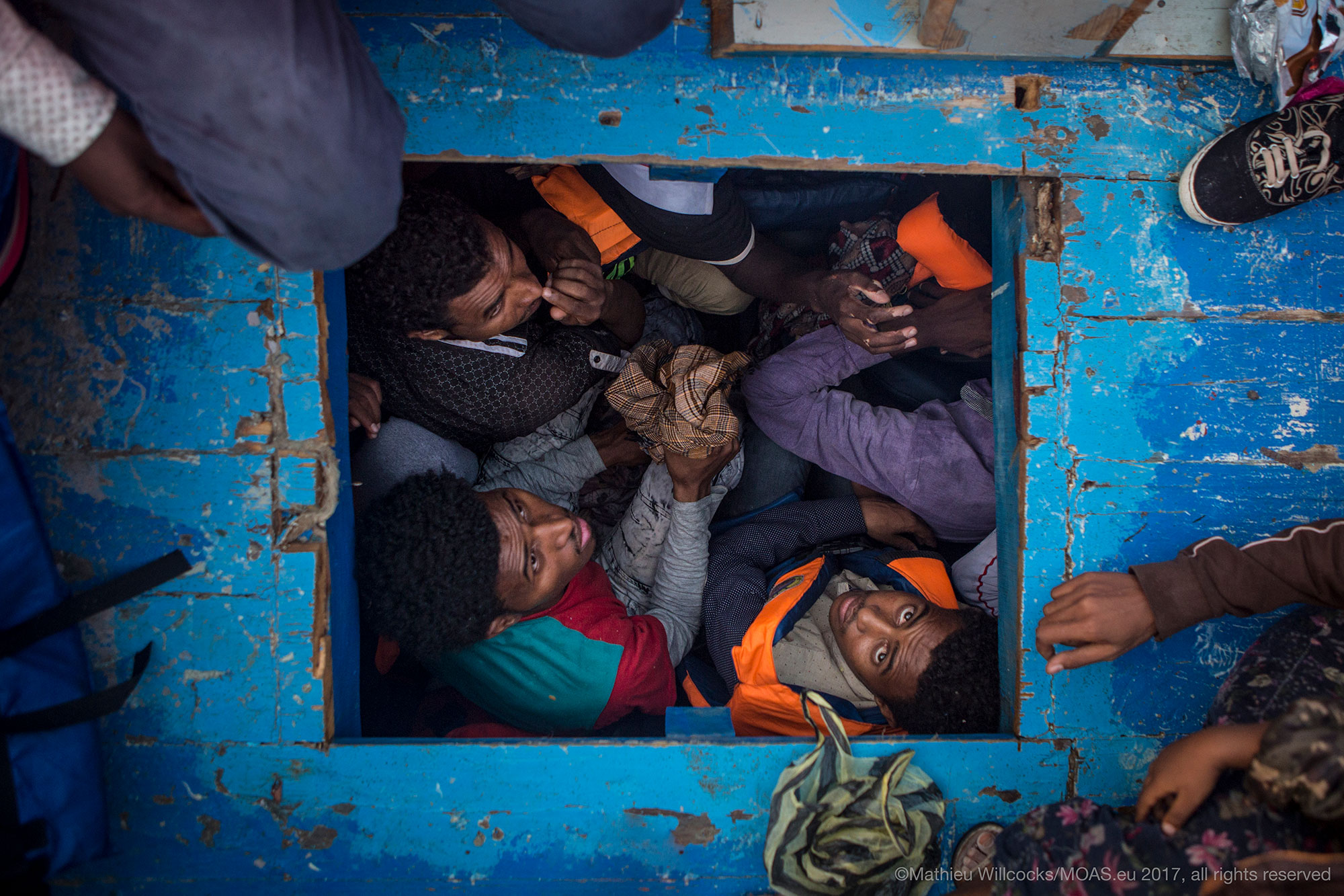 People attempting to cross the Mediterranean are pictured cramped inside a boat.