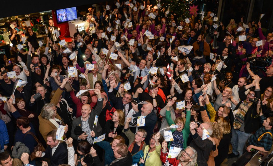 A sea of people wave flags as Coventry's City of Culture win is announced