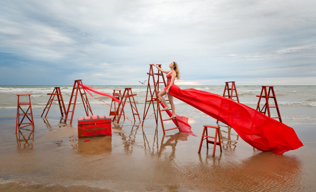 On a beach, a woman dressed in a billowing bright red dress is ascending a step ladder tethered to a large red chest surrounded by other red ladders.