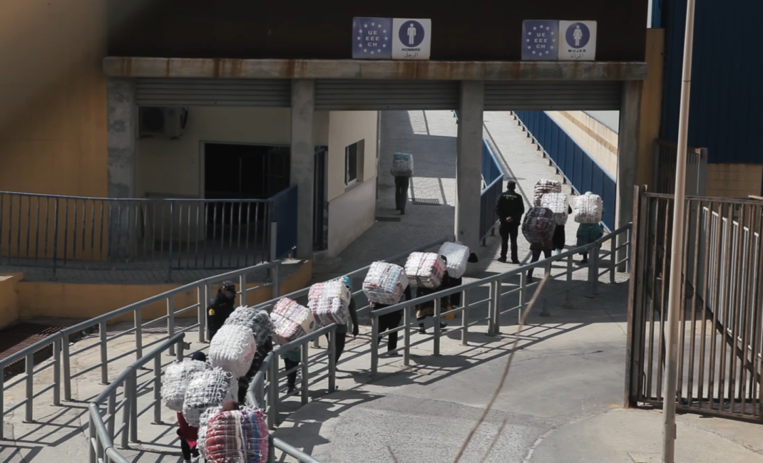 A line of women hunched over with heavy bales on their backs walk through border controls at Ceuta
