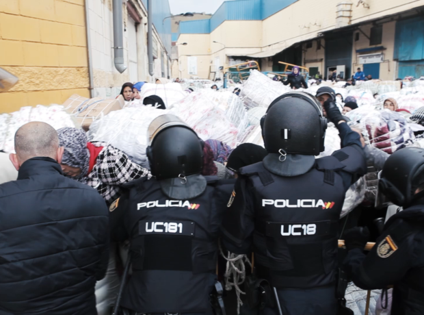 Police hold the surging crowd of women back at the border in Ceuta