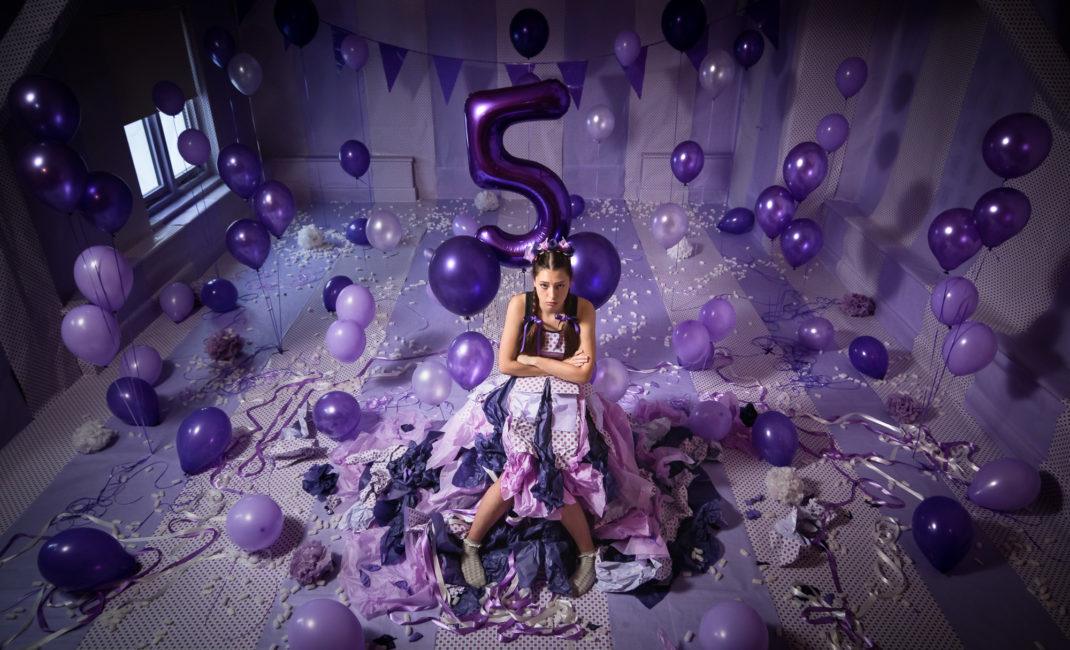 A girl sits alone in a purple room, surrounded by balloons and bunting, with a balloon in the shape of a 5 hovering behind her.