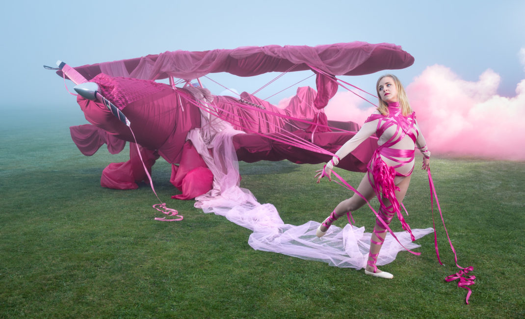 A ballet dancer is wrapped in bright pink ribbons, tethering her to an old-fashioned aeroplane, loosely swathed in pink fabric.