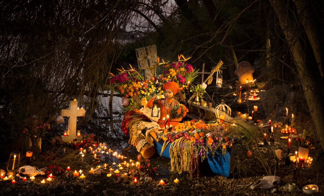 A young woman from South Africa's Xhosa tribe sits in a boat surrounded by flowers and candles.