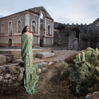 A woman stands, wrapped in green fabric, next to a crop of cacti and in front of ruins.