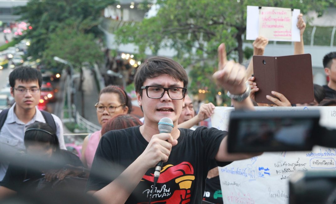 Rangisman Rome speaks in to a microphone and points his finger in the air during a protest in Thailand.