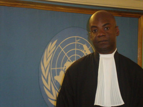 Charles Adeogun-Phillips stands in front of UN sign
