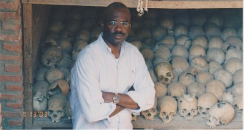 Charles Adeogun-Phillips stands in front of a collection of human bones