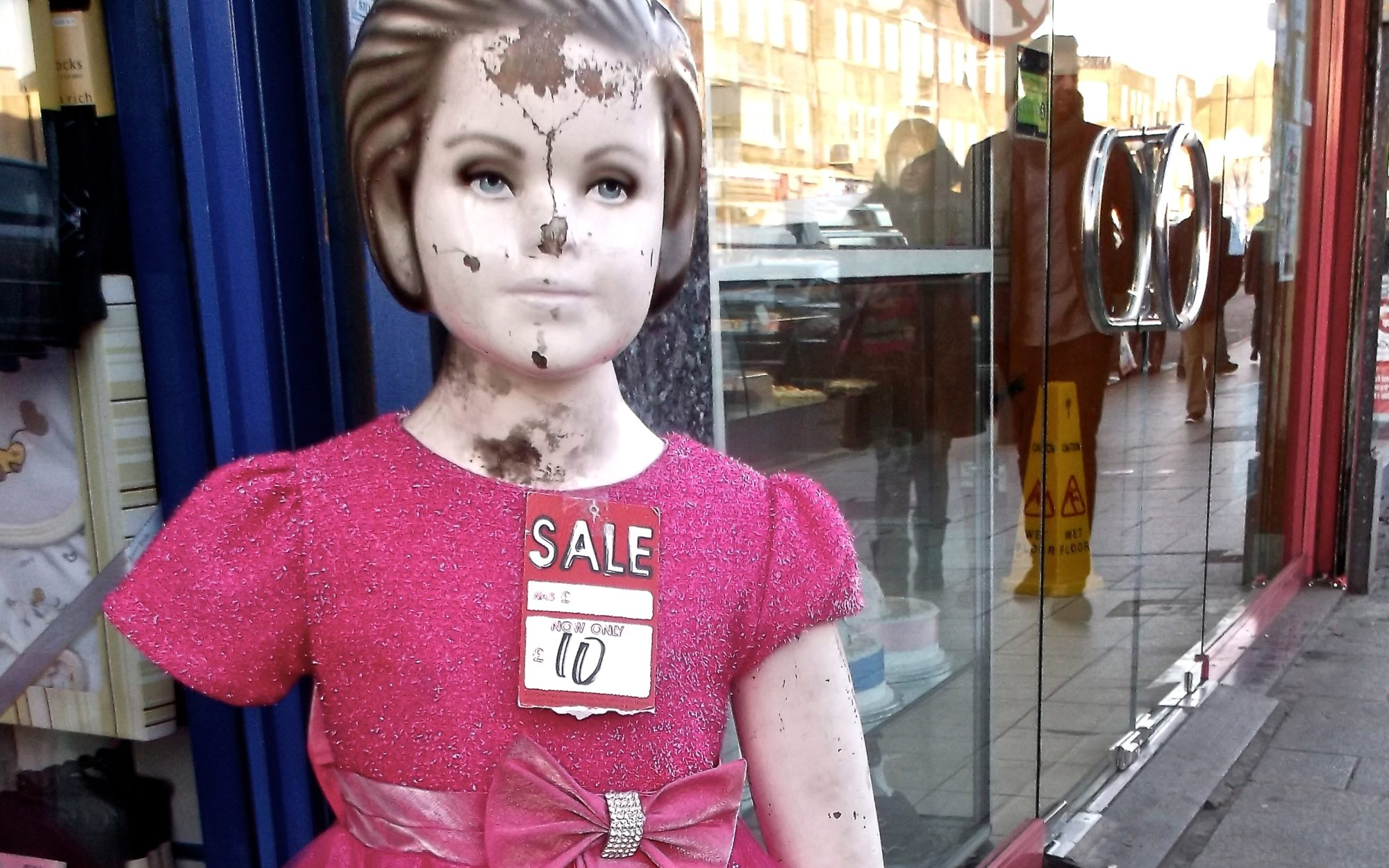 A defaced mannequin girl stands outside a shop, wearing a pink dress and a pricetag.