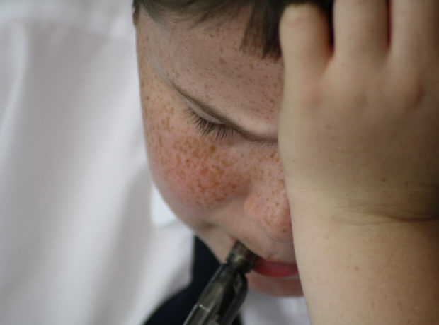 Boy in school uniform chews his pen as he frowns down at his work with his head in his hand. GCSE stress.