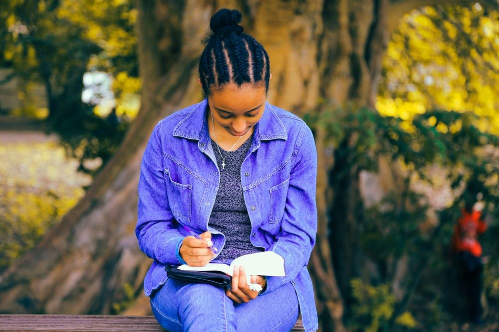 Woman wearing denim sit on a bench in front of a tree engrossed in a book.
