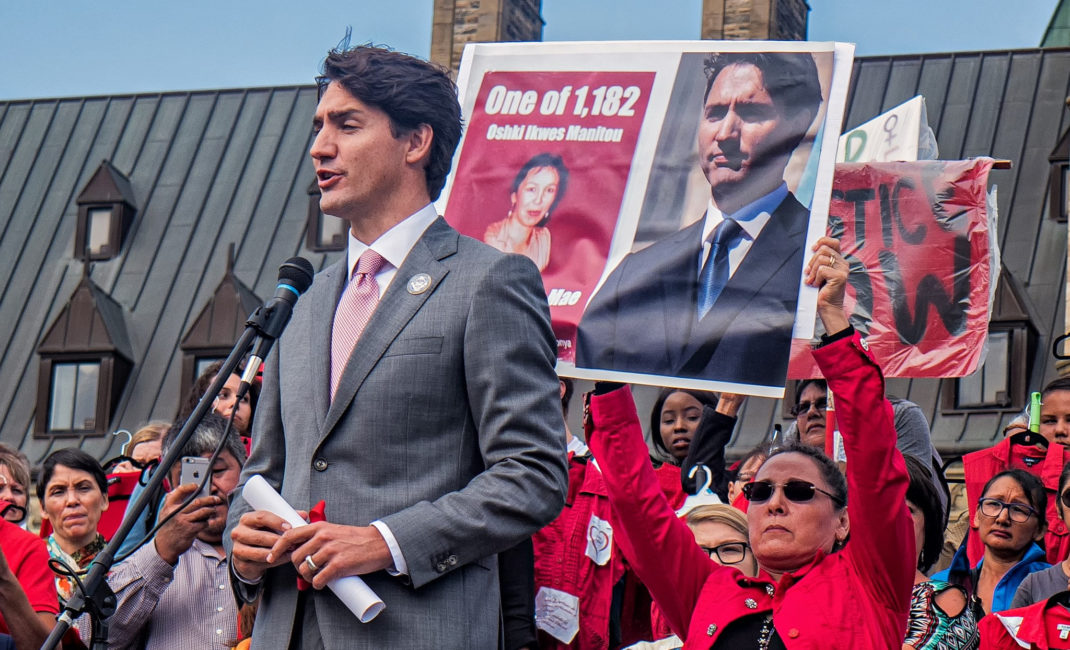 Behind Justin Trudeau, Maggie Cynwink holds up an image of her sister, Sonya Nadine Mae Cynwink, one of 1,182 recently missing or murdered Indigenous women and girls.
