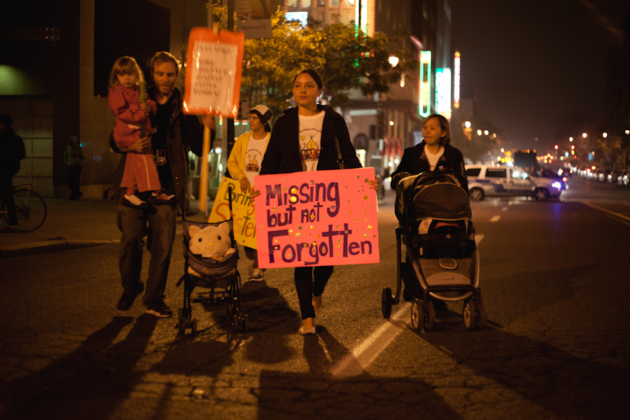 "At nighttime a woman walks, with prams being pushed on each side of her, carrying a placard reading ""Missing but not forgotten"" Families take to the streets in the annual ""Sisters in Spirit"" march and vigil"