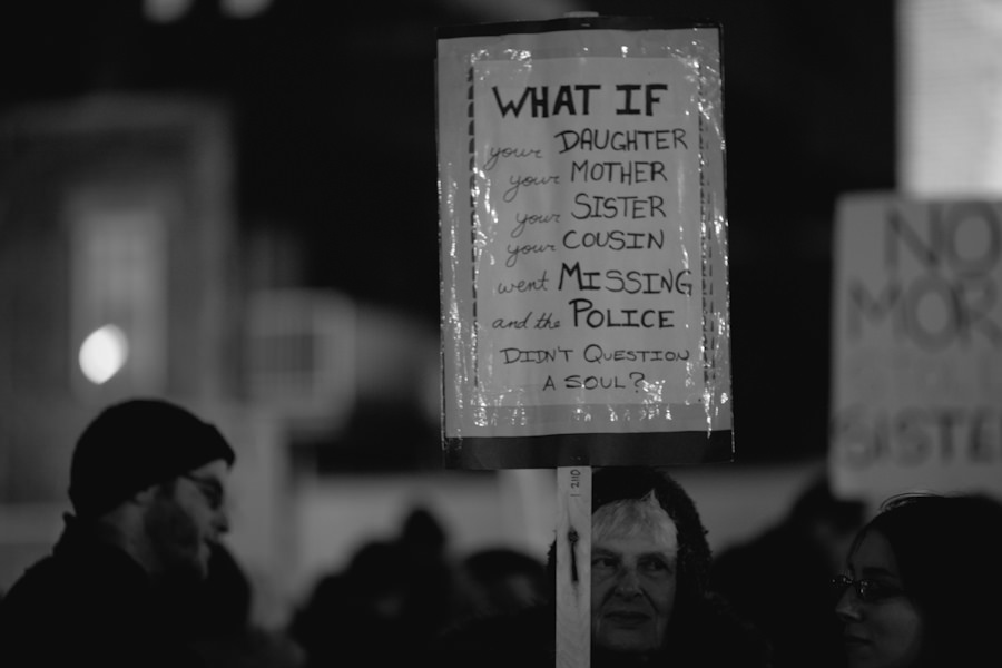 "In black and white, a placard over the crowd reads ""What if your daughter/mother/sister/cousin went missing and the police didnt question a soul?"""