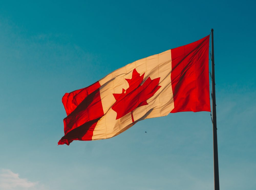 A large Canadian flag flying against a blue sky.