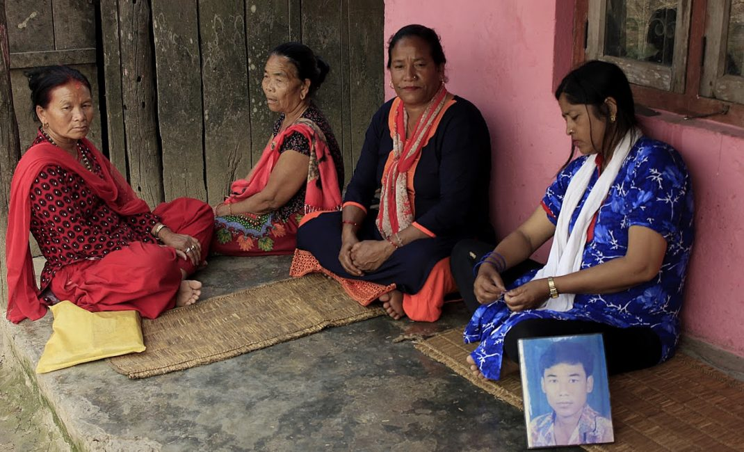 "Four women sit on grass mats on a porch next to a large head-and-shoulders picture of a man. Nepal's civil war: ""We are tired of promises, we need justice."""
