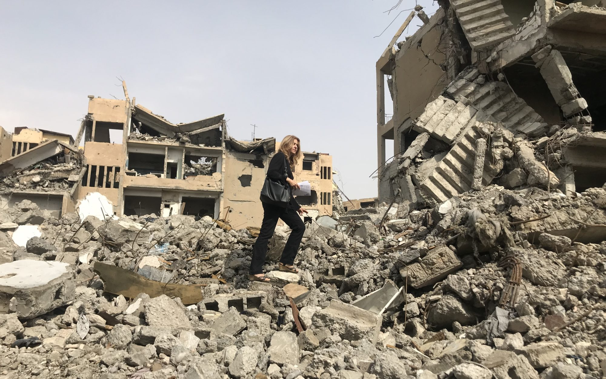 Anna Neistat of Human Rights Watch walks over buildings that have been reduced to rubble
