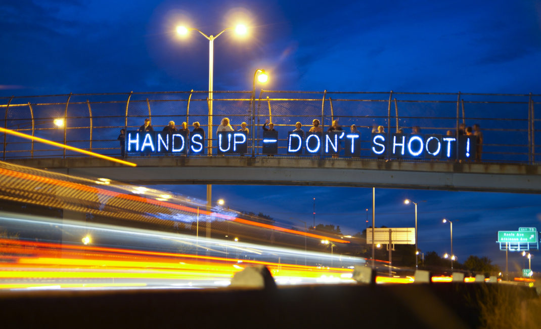 "People stand on a bridge with a banner reading ""Hands up - don't shoot!"" in protest against the shooting of Mike Brown in Ferguson"