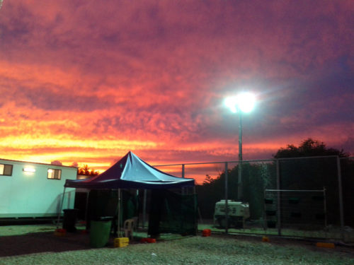 A deep pink sunset over a tent's peak. Refugees are held for a year or more in the fenced and tented refugee processing centre on Nauru where people who have tried to seek asylum in Australia were forcibly sent,