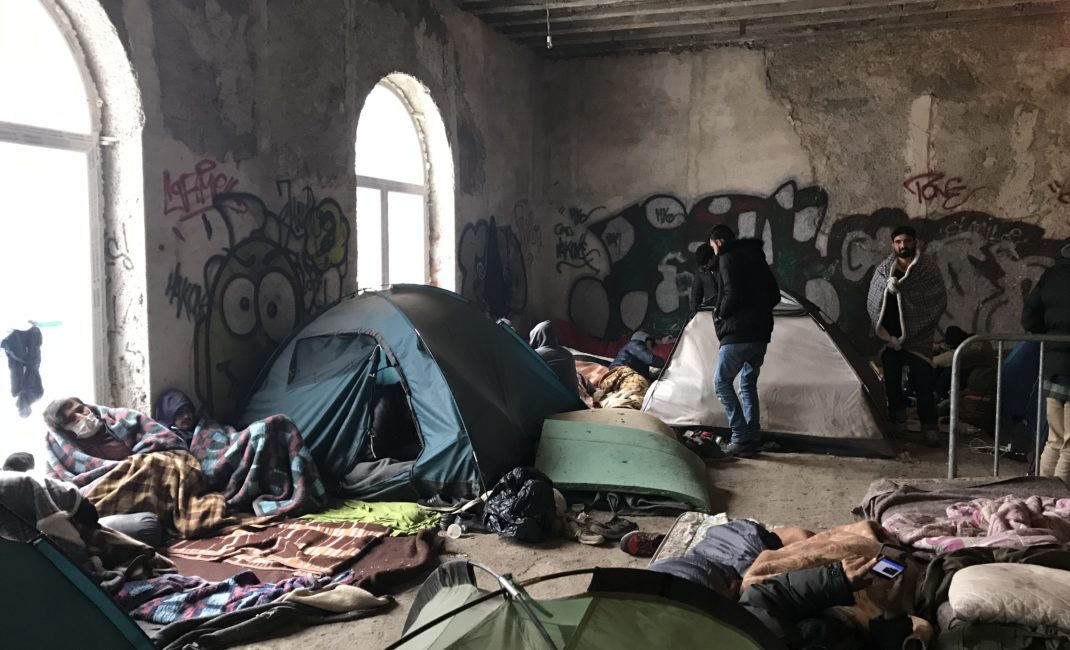 People huddle in blankets as tents, mattresses and rugs fill a bare, crumbling, graffiti-covered room.