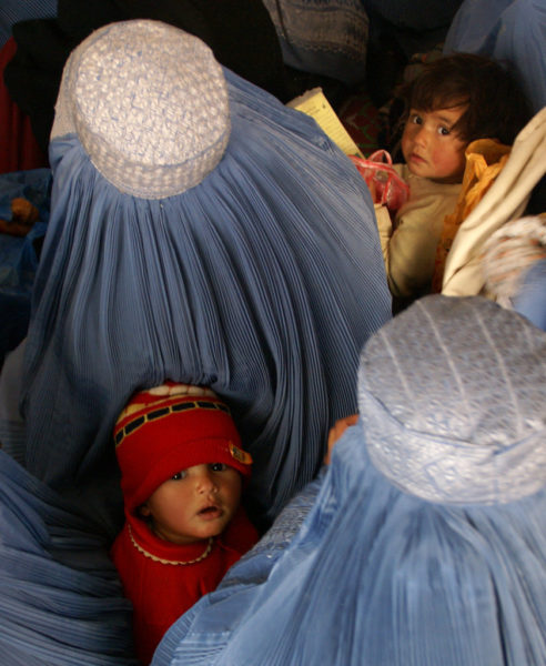 Two young children look up to the camera, sandwiched between women in tradition blue Afghan veils.