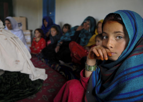 A young Afghan girl in a blue veil looks directly at the camera while a group of Afghan women and girls sit behind her out of focus