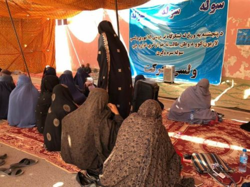 More than a dozen Afghan women wearing burqas sit on the floor on rugs beneath a sun-drenched tent during a sit-in protest in Helmand, Afghanistan.
