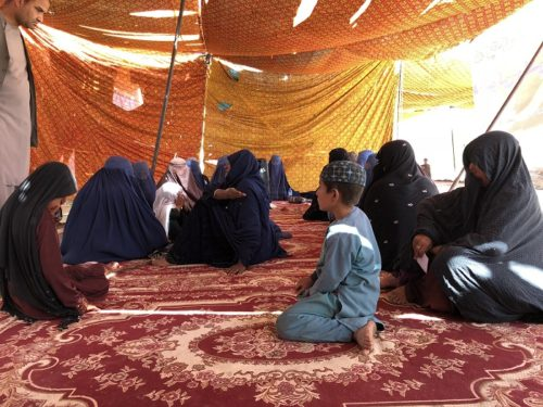 More than a dozen Afghan women wearing burqas sit on the floor on rugs beneath a sun-drenched tent during a sit-in protest in Helman, Afghanistan. A young boy sits with them.
