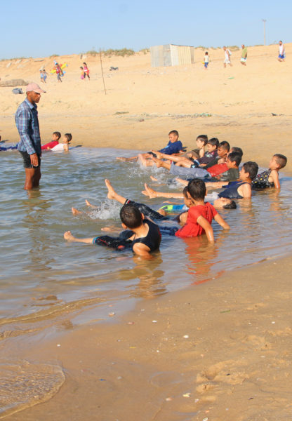 Children perfect their swimming strokes in Gaza's seawater pool.