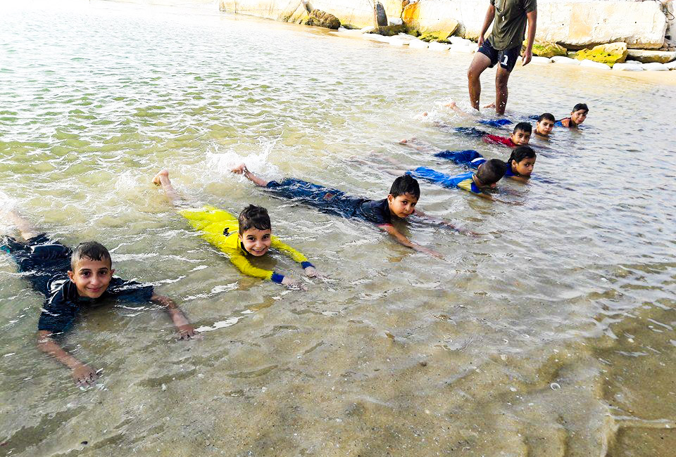 Children learning to kick at the swimming school on Gaza's beach.
