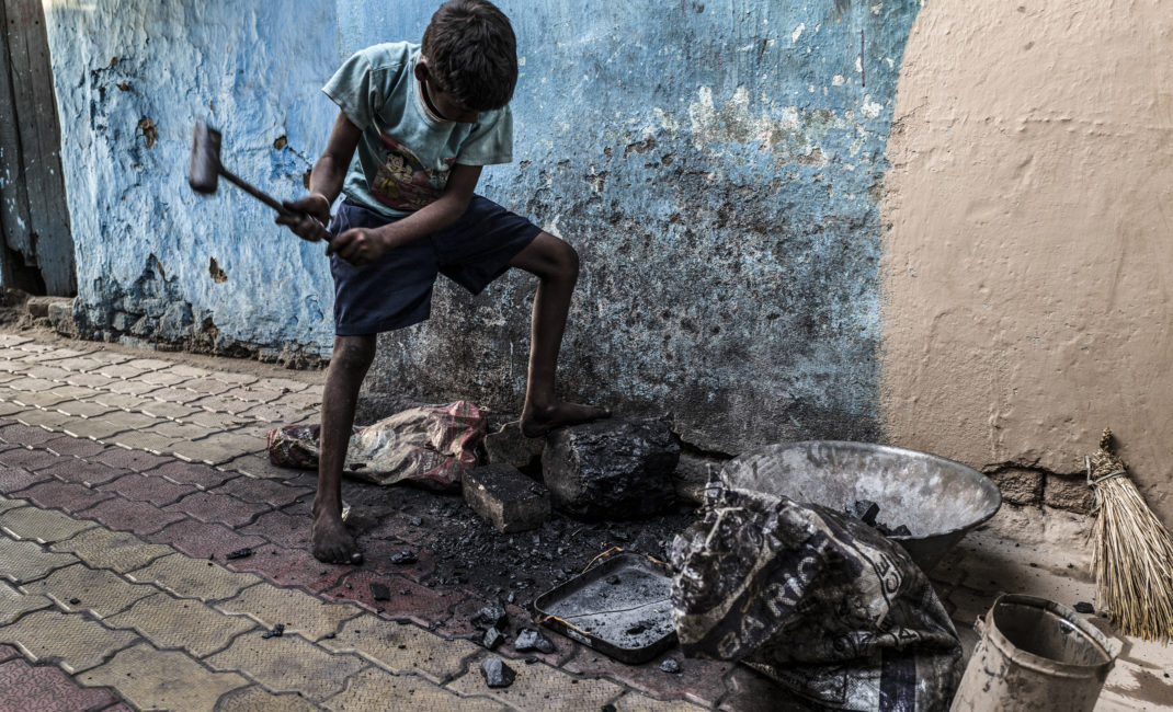 A young boy hammers a piece of coal to prepare a coal stove in Angarpathra