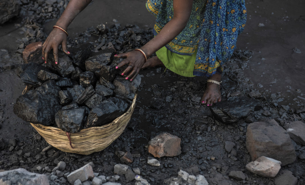 Pink nail varnish shines brightly against black coal where women mine with bare hands and feet
